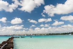 BRIDGETOWN, BARBADOS - 18 DE MARZO DE 2014: Playa de Bayshore en Barbados, Bridgetown Cielo nublado y agua del océano con el muel Imágenes de archivo libres de regalías