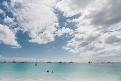 BRIDGETOWN, BARBADOS - 18 DE MARZO DE 2014: Playa de Bayshore en Barbados, Bridgetown Cielo nublado y agua del océano con el yate Imagen de archivo