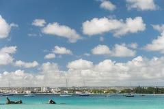 BRIDGETOWN, BARBADOS - 18 DE MARZO DE 2014: Playa de Bayshore en Barbados, Bridgetown Cielo nublado y agua del océano con el yate Fotos de archivo libres de regalías