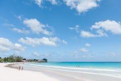 BRIDGETOWN, BARBADOS - 19 DE MARZO DE 2014: Playa de Bayshore en Barbados, Bridgetown Cielo nublado y agua del océano con la gent Imagen de archivo