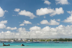 BRIDGETOWN, BARBADOS - MARCH 18, 2014: Bayshore Beach in Barbados, Bridgetown. Cloudy Sky and Ocean Water With Luxury Yacht and Bo Royalty Free Stock Photos
