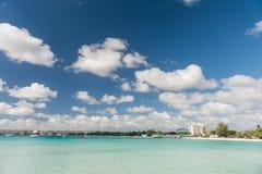 BRIDGETOWN BARBADOS - MARS 18, 2014: Bayshore strand i Barbados, Bridgetown Molnig himmel och havvatten med folk Fotografering för Bildbyråer