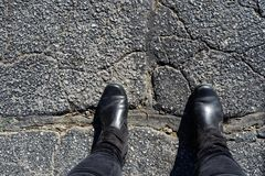 Bridging the Divide - Feet of woman in black boots stands with feet across big repair in cracked asphalt. She`s bridging the Divide - Feet of woman in black Stock Photos
