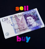 Bridging finance: temporary loan for new property. A macro concept image of twenty pound notes linking the word sell with the word buy both in colorful lower Stock Image