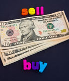 Bridging loan: help to buy a new property. A macro concept image of ten Dollar bills linking the word sell with the word buy both in colorful lower case letters Royalty Free Stock Photo