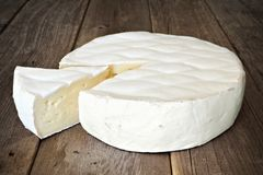 Brie cheese against a wood with cut slice Stock Photos