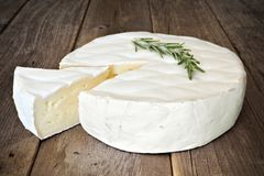 Brie cheese against wood with rosemary and slice cut Stock Photos
