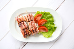 Brie cheese baked in bacon. On skewers Royalty Free Stock Photo