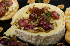 Brie cheese baked with nuts and grapes Stock Image