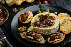 Brie cheese baked with nuts and grapes Stock Photography