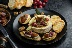 Brie cheese baked with nuts and grapes Royalty Free Stock Photos