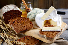 Brie cheese, black bread slices, roquefort and honey on a board Royalty Free Stock Photos