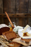 Brie cheese, bread slices, roquefort and honey on a board Royalty Free Stock Photography
