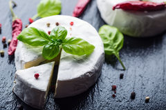 Brie cheese. Camembert cheese. Fresh Brie cheese and a slice on a granite board with basil leaves four colors peper and chili pepe Royalty Free Stock Image