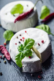 Brie cheese. Camembert cheese. Fresh Brie cheese and a slice on a granite board with basil leaves four colors peper and chili pepe Royalty Free Stock Photos