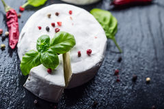 Brie cheese. Camembert cheese. Fresh Brie cheese and a slice on a granite board with basil leaves four colors peper and chili pepe Stock Image