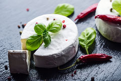 Brie cheese. Camembert cheese. Fresh Brie cheese and a slice on a granite board with basil leaves four colors peper and chili pepe Stock Photo