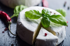 Brie cheese. Camembert cheese. Fresh Brie cheese and a slice on a granite board with basil leaves four colors peper and chili pepe Stock Photos