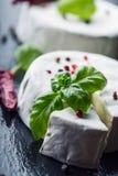 Brie Cheese Camembertost Ny Brie och en skiva på ett granitbräde med peper för färger för basilikasidor fyra och chilipepe Royaltyfria Bilder