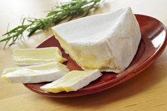 Brie cheese. Closeup of a piece and some slices of brie cheese in an earthenware plate Stock Photography