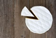 Brie cheese with cut slice, above view on rustic wood Stock Photography