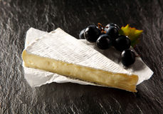 Brie Cheese and Fresh Black Grapes on Table Royalty Free Stock Photos