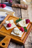 Brie cheese with fresh raspberries and crackers. Cheese platter. Brie soft cheese served with fresh raspberries and crackers on rustic wooden cutting board Royalty Free Stock Photo
