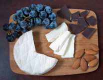 Brie cheese, grapes, chocolate and almonds on a wooden board. royalty free stock photos