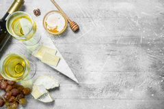Brie cheese with honey, grapes and white wine. On a rustic background stock photo