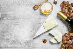 Brie cheese with honey, grapes and white wine. On a rustic background royalty free stock images