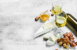 Brie cheese with honey, grapes and white wine. On a rustic background royalty free stock photography