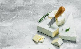 Brie cheese with knife. On a rustic background royalty free stock photo