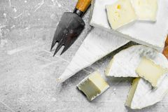 Brie cheese with knife. On a rustic background royalty free stock photos