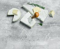 Brie cheese with knife. On a rustic background stock photography