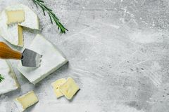Brie cheese with knife. On a rustic background stock image