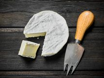 Brie cheese with knife. On a wooden background royalty free stock images