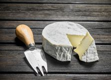 Brie cheese with knife. On a wooden background royalty free stock image