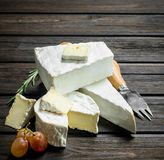 Brie cheese with knife. On a wooden background stock images