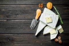Brie cheese with knife. On a wooden background royalty free stock photography