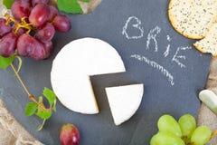 Brie Cheese med druvor arkivbild