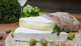 Brie cheese, olives and bread with white wine stock video