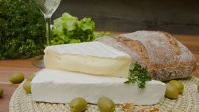 Brie cheese, olives and bread with white wine stock footage