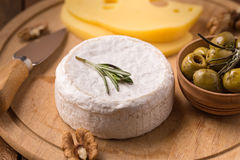 Brie cheese with olives. And knife on wooden plate Stock Image