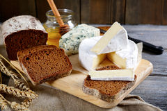 Brie cheese, rye bread slices, roquefort and honey on a board Royalty Free Stock Photography