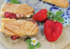 Brie cheese and strawberries. Brie cheese with strawberries on a bun with sesame seeds. soft focus royalty free stock images