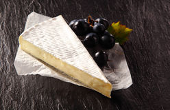 Brie Cheese Wedge and Black Grapes on Table Stock Image