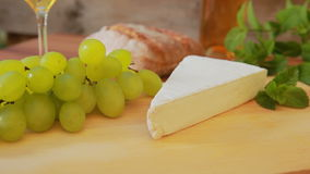 Brie cheese with white wine, grapes and bread. Circular movement of the camera around a piece of brie cheese on a wooden board. Against the background of wine stock video footage