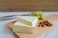 Brie cheese in wooden plate Royalty Free Stock Photos