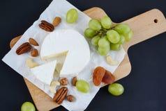 Brie con i dadi, i frutti secchi e l'uva verde in piatto di legno Immagini Stock