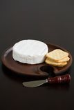 Brie and Crackers. Brie and butter cracker on a wooden cheese plate with cheese knife Stock Images